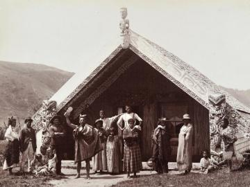 Maori chief and his family in front of a large Meeting House,  Te Wairoa